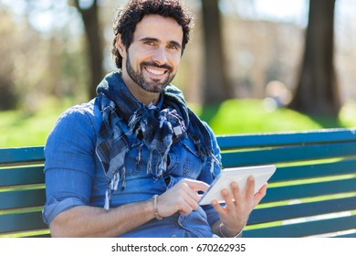 Handsome man sitting on a bench and using a digital tablet