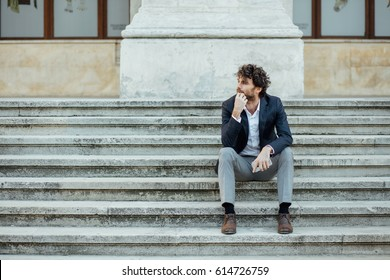handsome man sitting outside concerned on the stairs waiting for someone or something