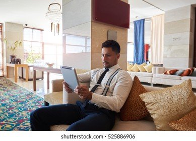 Handsome man skilled economist holding touch pad while siting in modern office interior near copy space,