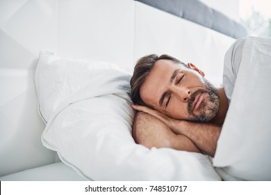 Handsome man sleeping in bed at home