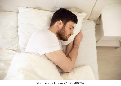 Handsome Man Sleeping Cozily in Bed at Home. Sweet Dreaming. Up Down View