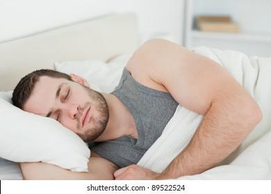 Handsome man sleeping in his bedroom