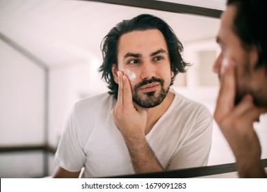 Handsome man smears face cream. Men's personal care. A young guy looks at himself in the mirror and puts cream on his face