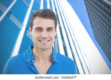 Handsome man smiling to the camera against view of modern building