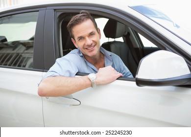 Handsome man smiling at camera in his car