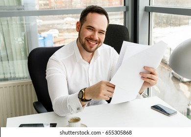 handsome man smiling at camera holding documents