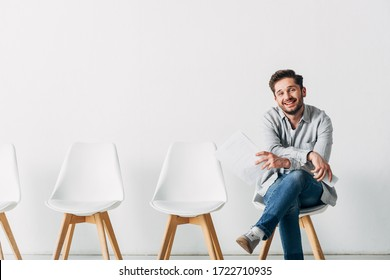 Handsome man smiling at camera while holding resume and smartphone in office