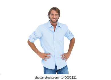 Handsome man smiling with his hands on hips on white background