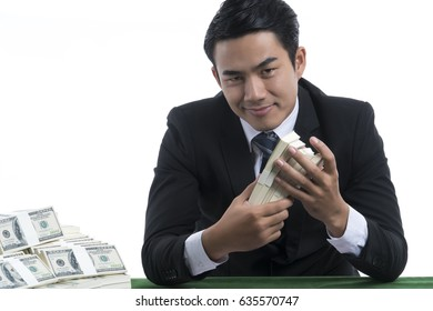 A Handsome man is smiling and holding piles of banknotes in hands, has a lot of dollars placed nearby, on green table, white background and copy space, casino business concept