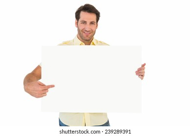 Handsome man smiling and pointing white poster on white background