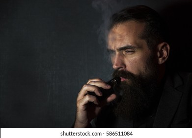 A handsome man smoking an electronic cigarette on a dark grey background