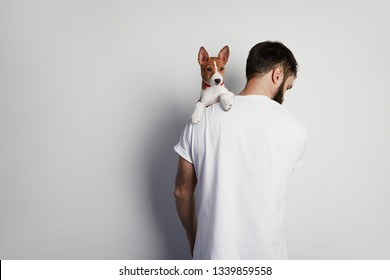 Handsome man snuggling and hugging his basenji puppy dog, close friendship against a white background