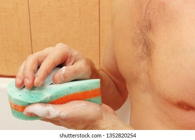 Handsome man soaping a green sponge with soap