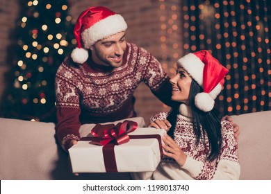 Handsome man in soft ornament sweater hold big package give it to cheerful careless carefree brunette lady who sit in cozy living room couch modern house interior with sparkles garland on pine tree