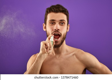 A handsome man spraying breath to refresh his mouth before the date. close up portrait. pastime. morning routine. secrets of fresh breath