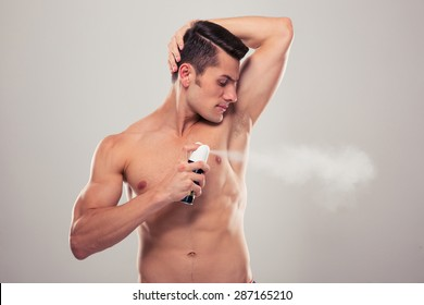 Handsome man spraying deodorant over gray background