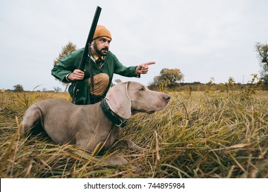 handsome man squatting with a dog and hunting down an animal