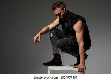 Handsome man squatting and getting off a chair while wearing a black jeans vest on gray studio background