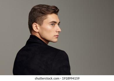 gut aussehender Mann, der sich hinter dem modischen Haarstil erhebt