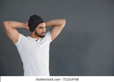 Handsome man standing with hands behind back against grey background