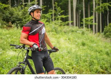 Handsome man standing with his bicycle near forest and looking away.