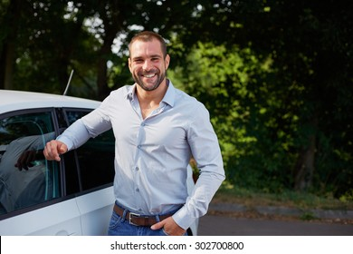 Handsome man standing leaning on car