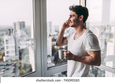 Handsome man is standing near open panoramic window with cup of coffee and smart phone in hands. Talking on mobile phone. Beautiful view on city.