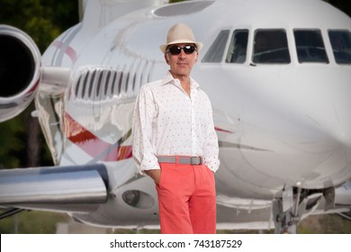 Handsome man standing next to a private jet
