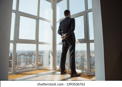 Handsome man standing next to the window, looking out. Bearded attractive gentleman in an elegant stylish clothes thinking. Back view