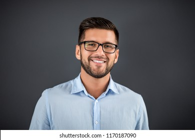 Handsome man standing over dark grey background and looking on camera. Portrait man concept.