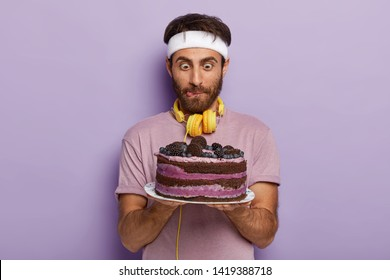 Handsome man stares surprisingly at big tasty cake, licks lips, has strong desire to eat dessert, wears headband, t shirt and headphones, poses over purple background. Sweet junk food concept