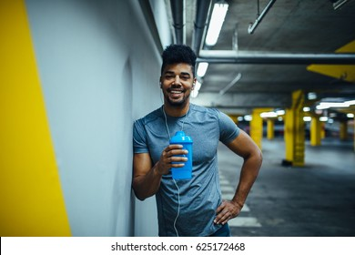 Handsome man stopping for a water while exercising.