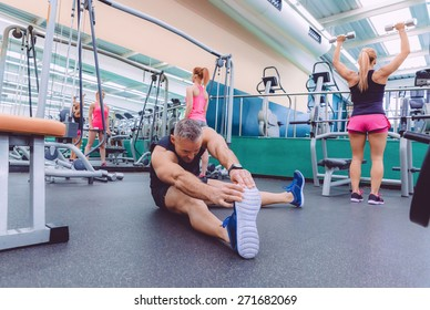 Handsome man stretching in a fitness center and two beautiful women doing exercises with dumbbells in the background
