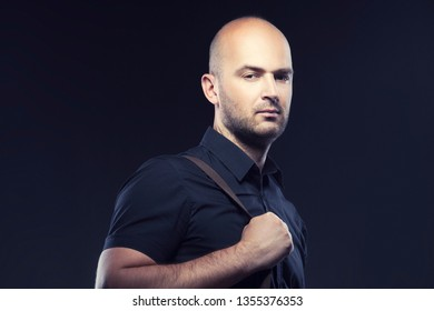 Handsome man studio portrat. Dark background. Bald head, beard, fashion black shirt
