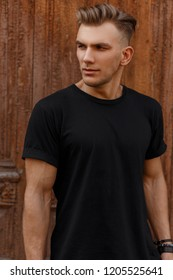 Handsome man with stylish hairstyle in fashionable black mockup t-shirt stands near a wooden vintage door