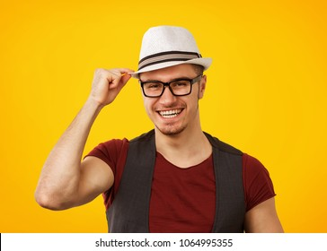 Handsome man in stylish hat and glasses standing on yellow background smiling at camera and touching hat.