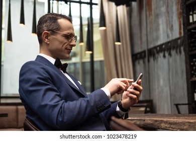 handsome man in stylish suit using smartphone at restaurant