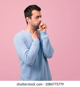 Handsome man is suffering with cough and feeling bad on pink background