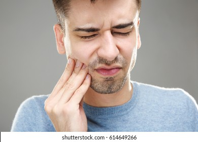Handsome man suffering from toothache on grey background, closeup