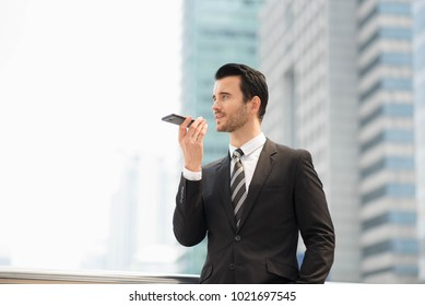 Handsome man in suie holding laptop and sending voice massage with a mobile phone ,Business city success industry concept.