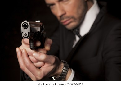 handsome man in a suit aim with a gun