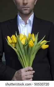 handsome man in the suit with a bunch of yellow tulips