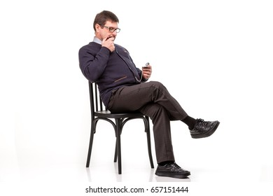 A handsome man in a suit and glasses, sits, with a pipe for smoking; White background