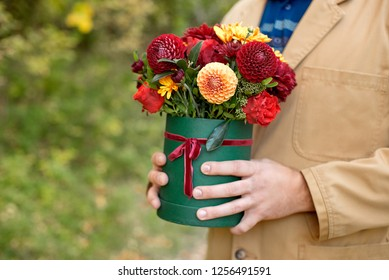 Handsome man in suit holding hands a festive green box with delicate flowers. A gift to women's day. Close-up side view. The concept of wedding, birthday, events, celebrations, flower delivery