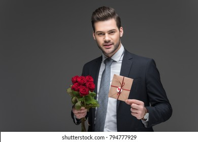 handsome man in suit holding red roses and envelope for valentines day, isolated on grey
