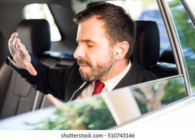 Handsome man in a suit listening to his favorite song and getting pumped up before going to work in the morning