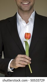 handsome man in the suit with a red tulip