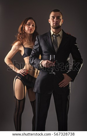 57166ddc82 Handsome man in a suit and sexy young woman in lingerie and stockings.  Portrait of a sexy couple on a dark background. - Image