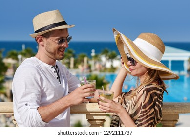 Handsome man in sun hat and sunglasses is talking to his wife on the balcony  of 5b76a2cd9aeb
