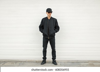 Handsome man with sunglasses in black modern jacket, baseball cap and black Sneakers near the white blinds